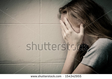 stock-photo-one-sad-woman-sitting-on-the-floor-near-a-wall-and-holding-her-head-in-her-hands-154342955